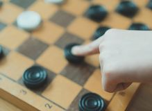 Child playing checkers board game. Close-up view stock photography