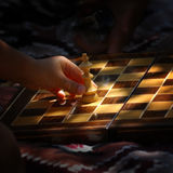 Child Playing Chess. A three year old child moves a king game piece on a chess board Royalty Free Stock Image