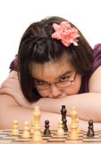 Child Playing Chess. A young girl thinking about her next move in a game of chess Royalty Free Stock Image