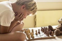 Child playing chess. Child boy playing chess at home, intellectual game, tint and selective focus Stock Photos