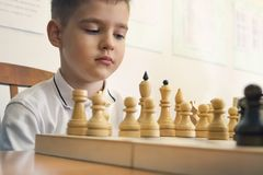 Child playing chess, on white background. . Stock Photo