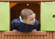 Child playing in a children playhouse. Royalty Free Stock Photos