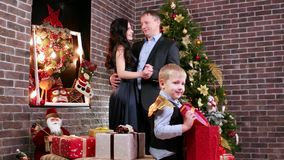 Child playing with Christmas gifts on the background lovers parents dancing near the Christmas tree, a happy family on stock footage