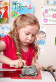 Child  playing with clay in classroom. Stock Photos