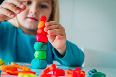 Little girl playing with clay molding shapes, kids crafts stock image