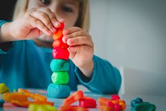 Little girl playing with clay molding shapes, kids crafts stock photos
