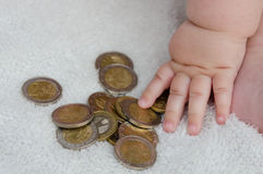 Child playing with coins. Child hand playing with coins Stock Photo