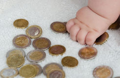Child  playing with coins. Child hand playing with coins Royalty Free Stock Photography