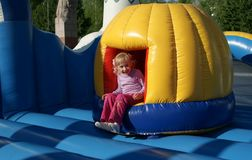 Child playing in bouncy castle. Child playing in color bouncy castle outdoor Royalty Free Stock Photography