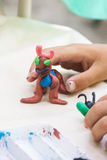 Child playing with colorful clay making animal figures. closeup on hands.  royalty free stock photos