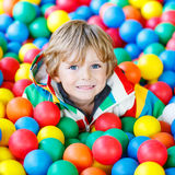 Child playing at colorful plastic balls playground. Happy little kid boy playing at colorful plastic balls playground high view. Adorable child having fun Stock Photo