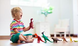 Child playing with toy dinosaurs. Kids toys