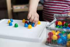 Child playing with colorful toys sitting at a window. Little boy Stock Photo