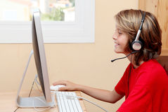 Child playing with computer. Happy child playing with computer with earphones Royalty Free Stock Photos