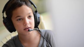 Child playing on the computer with headphones stock footage