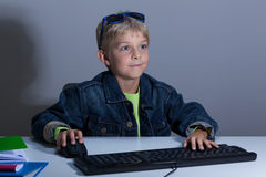 Child playing on computer at night. Horizontal Stock Photo