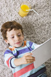 Child playing with digital tablet stretched on a carpet Stock Photos
