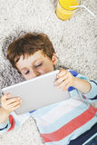 Child playing with digital tablet stretched on a carpet Royalty Free Stock Image