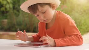 Child playing with digital tablet on summer nature background stock footage