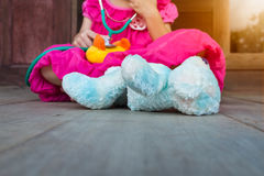 Child playing doctor or nurse with plush toy bear at home. Royalty Free Stock Photo