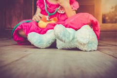 Child playing doctor or nurse with plush toy bear at home. Vinta Royalty Free Stock Photos