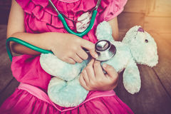 Child playing doctor or nurse with plush toy bear at home. Vinta Royalty Free Stock Images