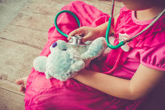 Child playing doctor or nurse with plush toy bear at home. Vinta. Child playing doctor or nurse with plush toy bear with bright sunlight at home. Happy girl Stock Photos