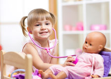 Child playing doctor role game examinating her. Child girl playing doctor role game examinating her doll using stethoscope sitting in playroom at home, school or Stock Image