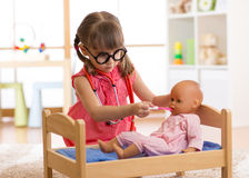 Child playing doctor with toy. Child playing doctor with doll at home Stock Photos