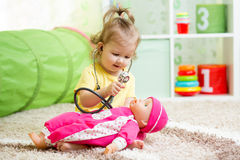 Child playing doctor with toy. At home Stock Image