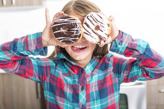 Child playing with donuts in her hands putting them on her face. A child playing with donuts in her hands putting them on her face royalty free stock photo