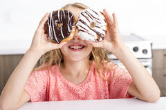 Child playing with donuts in her hands putting them on her face. A child playing with donuts in her hands putting them on her face royalty free stock image