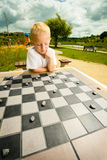 Child playing draughts or checkers board game outdoor. Draughts board game. Little boy clever child kid playing checkers thinking, outdoor in the park. Childhood stock images