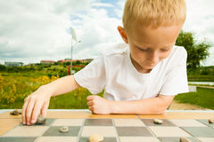 Child playing draughts or checkers board game outdoor. Draughts board game. Little boy clever child kid playing checkers thinking, outdoor in the park. Childhood royalty free stock image