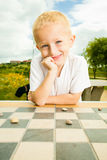 Child playing draughts or checkers board game outdoor Royalty Free Stock Photography