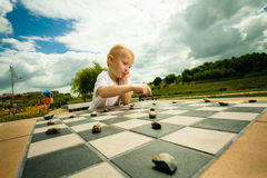 Child playing draughts or checkers board game outdoor. Draughts board game. Little boy clever child kid playing checkers thinking, outdoor in the park. Childhood stock photo