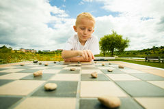 Child playing draughts or checkers board game outdoor Royalty Free Stock Photos