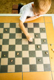 Child playing draughts or checkers board game outdoor. Draughts board game. Little boy clever child kid playing checkers thinking, outdoor in the park. Childhood stock image