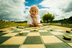 Child playing draughts or checkers board game outdoor. Draughts board game. Little boy clever child kid playing checkers thinking, outdoor in the park. Childhood royalty free stock images