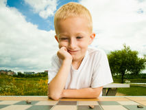 Child playing draughts or checkers board game outdoor. Draughts board game. Little boy clever child kid playing checkers thinking, outdoor in the park. Childhood royalty free stock photography