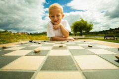 Child playing draughts or checkers board game outdoor. Draughts board game. Little boy clever child kid playing checkers thinking, outdoor in the park. Childhood stock photos