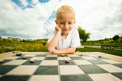 Child playing draughts or checkers board game outdoor Stock Photography