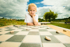 Child playing draughts or checkers board game outdoor Royalty Free Stock Photo
