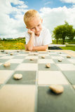 Child playing draughts or checkers board game outdoor. Draughts board game. Little boy clever child kid playing checkers thinking, outdoor in the park. Childhood stock photography