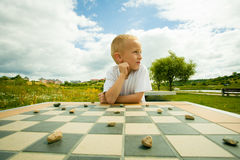 Child playing draughts or checkers board game outdoor. Draughts board game. Little boy clever child kid playing checkers thinking, outdoor in the park. Childhood royalty free stock photo