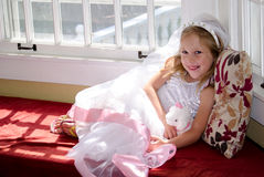 Child playing dressup. A little girl sits in a window seat in a costume dress up wedding gown Stock Photos
