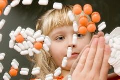Child playing with drugs. Reflection in the mirror girl with pills Stock Images