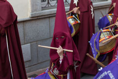 Child playing drum in day procession during Semana Santa Stock Photos