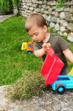 Child playing with dump truck Stock Photo