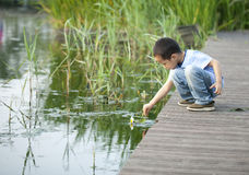 Child playing on the edge of a wooden pontoon next. Asian child playing on the edge of a wooden pontoon next to the water Stock Photos